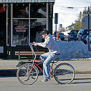 """SHOT 3/16/10 5:33:41 PM - A Crested Butte local rides his cruiser bike down Elk Avenue with his dog in Crested Butte, Co. In the background is the Crested Butte Mountain Heritage Museum and Mountain Bike Hall of Fame. Crested Butte is a Home Rule Municipality in Gunnison County, Colorado, United States. A former coal mining town now called """"the last great Colorado ski town"""", Crested Butte is a destination for skiing, mountain biking, and a variety of other outdoor activities. (The Hardware Store & Tony's Conoco Station) This building began operating as a hardware store in 1883. It was the town's first gas station..(Photo by Marc Piscotty / © 2010)"""
