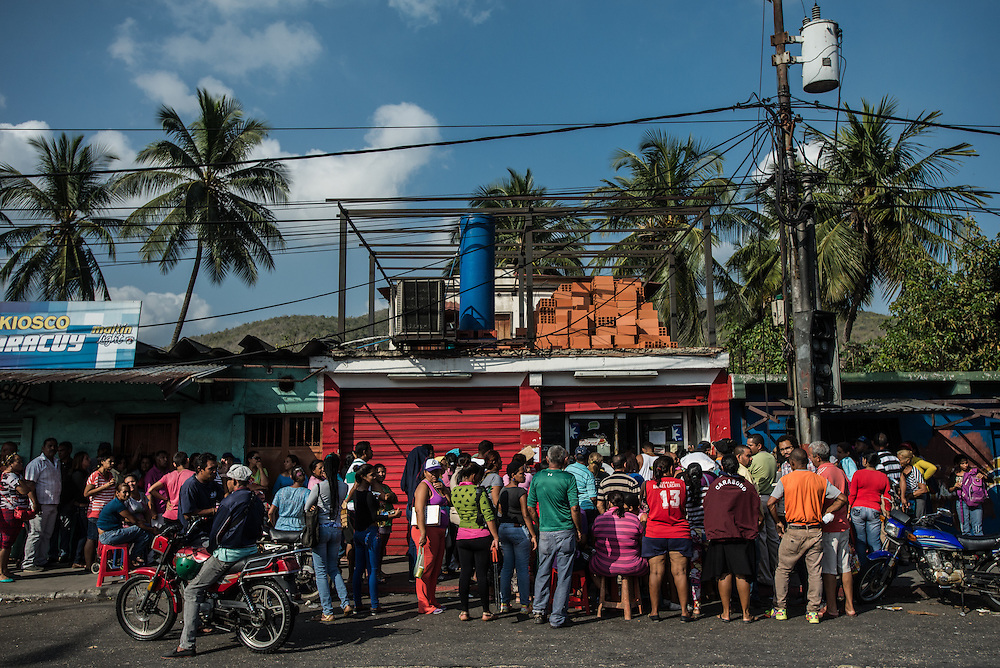 PUERTO CABELLO - JANUARY 27, 2016: Down the hillside in Puerto Cabello, a line formed in front of a state-run grocery store, as hundreds of people looked for food on a recent morning in the port town. Many had arrived at 5:30 a.m. when rumor had it a delivery truck had reached the store. It was now a quarter past 10 a.m. and many people still waited in the sun. A policeman with a pistol now manned the door, letting in a dozen at a time.  Yesterday there were beans, flour and milk for sale. Today there was only cooking oil and powdered milk.   PHOTO: Meridith Kohut for The New York Times