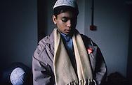 United Kingdom. Birmingham. Birmingham:  In spite of this Orthodox Islamic education, the children are not unaware of the occidental society.  This boy in prayer wears a coca-cola badge.  Birmingham  UnitedKingdom     /  Birmingham: malgré cet enseignement islamique orthodoxe, les enfants ne sont pas insensibles à la société occidentale. Ce garçon en prière arbore un badge Coca Cola. Coventry islamic boy school .  Birmingham  Grande Bretagne   /  R00017/    L0007462  /  R00017  /  P0005560