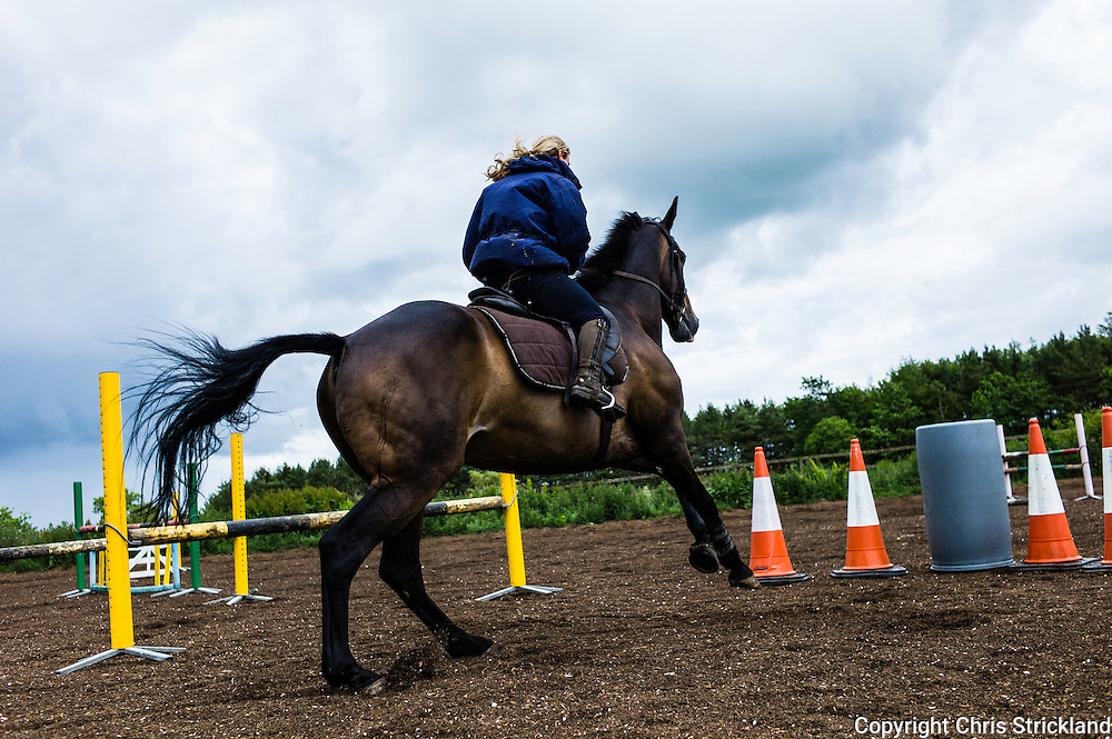 Ancrum, Jedburgh, Scottish Borders, UK. 7th July 2015. Four Star eventer Emily Galbraith schools eventer 'Johnnie' at home in the Borders in sunshine and showers. © Chris Strickland / Alamy Live News