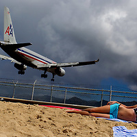 St. Martin St. Maarten -- February 2011 -- Sunbathers watch an American Airlines plane land over Maho Beach at Sunset Bar & Grill near Princess Juliana Airport on the Caribbean island of St. Martin / St. Maarten, which is split between France and the Netherlands.  (Photo by Chip Litherland)