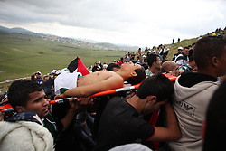 The body of Mohammed al-Fandi is carried up the mountain to Maroun al-Ras after he was show by Israeli soldiers during a 15 May 2011 protest at the border in south Lebanon by Palestinian refugees calling for the right to return home.