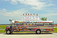 MR. Model relased photo. Six ballerinas dance and balance on top of a Diablo Rojo in la Cinta Costera, Panama´s coastal highway.
