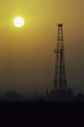 Stock photo of the silhouette of an oil and gas rig at sunset in Texas