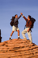 two men clasping hands on top of a mountain at sunset