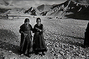 Two cataract blind women cross a glacial stream and harsh desert like landscape to the Eye Camp in Charang, Mustang Nepal 1992 conducted by Dr Sanduk Ruit and Tilganga Institute of Opthalmology.