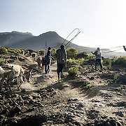 Villagers including Takele Lemma, 18, (right) are carrying supplies used to cap the water source in Adi Sibhat, Tigray, Ethiopia.