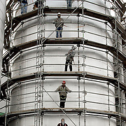 Workers from Miller Insulation of North Dakota remove scaffolding from the cook water tank Monday, December 8, 2003, after wrapping it with insulation. Water for the plant is pumped from a nearby well, and is recycled back into the system to be used again.
