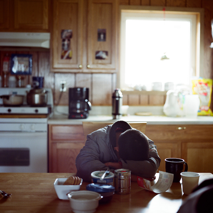 NEWTOK, ALASKA - 2008: Boy sleeping at dining room table at Peter Johns home.