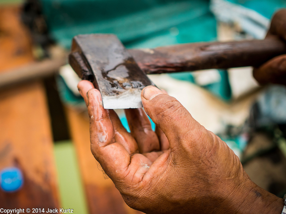 16 SEPTEMBER 2014 - SANGKHLA BURI, KANCHANABURI, THAILAND: A worker checks the edge on his axe while working on the repair of the Mon Bridge. The 2800 foot long (850 meters) Saphan Mon (Mon Bridge) spans the Song Kalia River. It is reportedly second longest wooden bridge in the world. The bridge was severely damaged during heavy rainfall in July 2013 when its 230 foot middle section  (70 meters) collapsed during flooding. Officially known as Uttamanusorn Bridge, the bridge has been used by people in Sangkhla Buri (also known as Sangkhlaburi) for 20 years. The bridge was was conceived by Luang Pho Uttama, the late abbot of of Wat Wang Wiwekaram, and was built by hand by Mon refugees from Myanmar (then Burma). The wooden bridge is one of the leading tourist attractions in Kanchanaburi province. The loss of the bridge has hurt the economy of the Mon community opposite Sangkhla Buri. The repair has taken far longer than expected. Thai Prime Minister General Prayuth Chan-ocha ordered an engineer unit of the Royal Thai Army to help the local Mon population repair the bridge. Local people said they hope the bridge is repaired by the end November, which is when the tourist season starts.    PHOTO BY JACK KURTZ