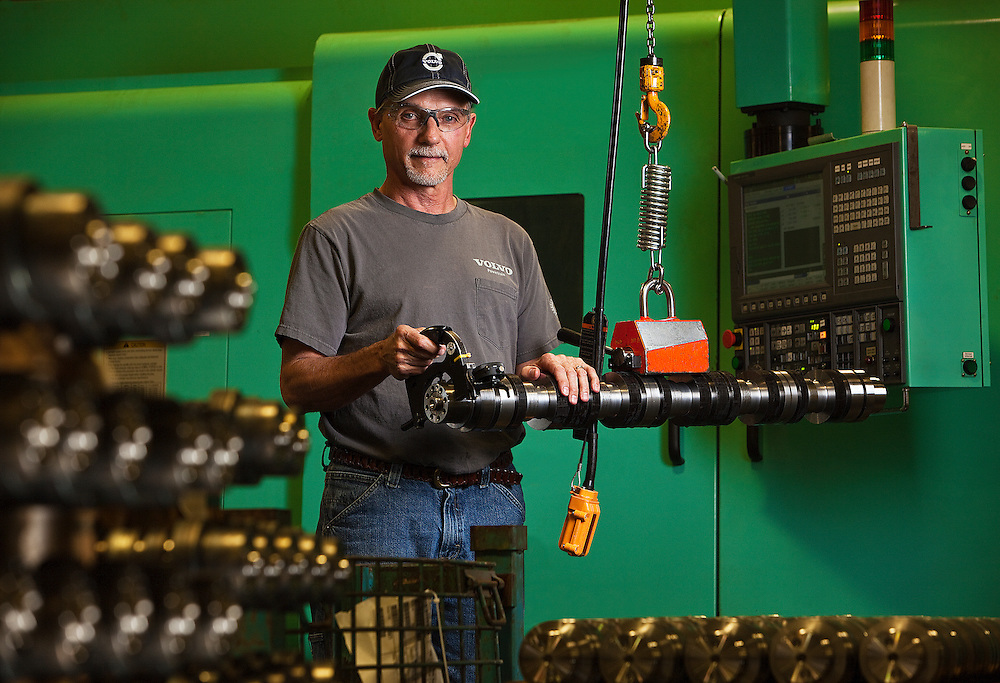 Technician measuring camshaft tolerances after machining