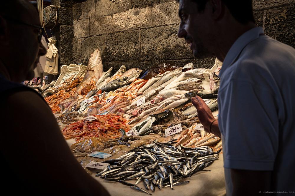 Fishmonger selling fish to a client at La Pescheria. Catania, Sicily, Italy