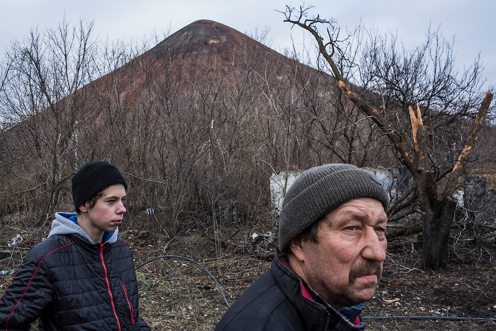 DONETSK, UKRAINE - FEBRUARY 3, 2015: Neighbors Danyl Vasylenko, left, and Aleksandr Zaytsev, take a walk near the house where Zaytsev's wife and son were killed by shelling over the summer in the Petrovsky district of Donetsk, Ukraine. The neighborhood has been under heavy shelling for the past four days, and a brief pause allowed a few residents to leave their basement hiding places for some fresh air. Behind them is a hill of mine tailings. CREDIT: Brendan Hoffman for The New York Times