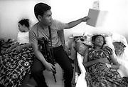 A young Indonesian member of BRIMOB, Julian Intarina comforts his sister Numun at Farkinah Hospiotal in Banda Aceh. 06/01/05
