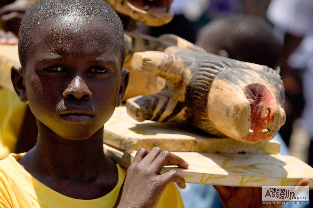 A boy holds up a wooden carving of a lion, emblem of the #4 Asafo company duing the parade held on the occasion of the annual Oguaa Fetu Afahye Festival in Cape Coast, Ghana on Saturday September 6, 2008..