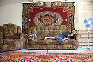 An old woman stops for a rest in her home in the Chalabixan camp for internally displaced people from Nagorno-Karabakh, located near Sheki, Azerbaijan.