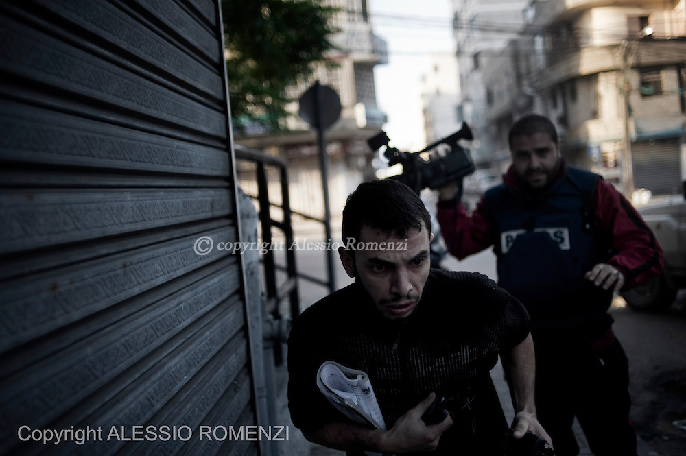 Gaza City: Journalists run away from an explosion as Israeli air-force fired a rocket on Al-Aqsa TV station in Gaza City. November 18, 2012. ALESSIO ROMENZI