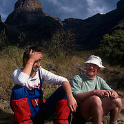 Gavin Raubenheimer and Andre Dalais back at Keith Bush Camp in the uMhlwazini Valley, after summiting Monk's Cowl 3234m (10,611ft), behind.  Ukhahlamba-Drakensberg Park, KwaZulu-Natal, South Africa.  Nikon F90, 28-70/3.5. Fuji RD. October 1995