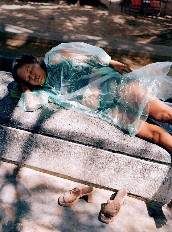 A woman sleeps in a plastic raincoat on Pattaya's beach promenade.