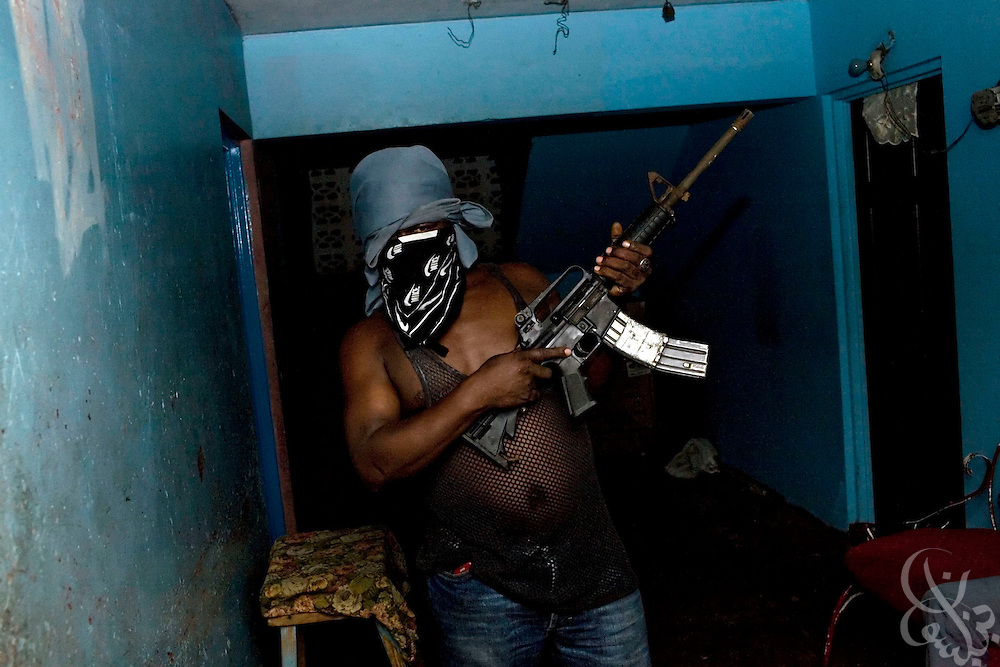 "A Jamaican gang member wields an automatic assault rifle in a public housing hallway December 25, 2008 in a section of the gang-controlled Rema ""Garrison."" Gunmen in the garrisons are well armed with weapons flowing in from Colombia, Haiti and the United States and this abundance of guns is certainly one of the factors fueling Jamaica's high murder rate."