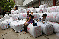 A Chinese woman sits on bags of emergency supplies in Longmen Village of Lushan County, Sichuan Province, China, 22 April 2013. The Lushan Earthquake in Sichuan Province on 20 April 2013 resulted in 186 people dead, 21 missing, 11248 injured. About 1.72 million people were affected by the quake, while an initial estimate by the International Red Cross on Saturday put the number needing emergency shelter, water and food at 120,000. The China Earthquake Administration (CEA) recorded a magnitude 7.0 earthquake, while the US Geological Survey said it had measured 6.9.