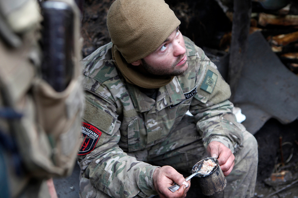 Cowboy takes a lunch break in a trench position at the frontline of Donetsk.<br /> <br /> +++   +++ The Boom Stick Brotherhood +++   +++  <br /> <br /> Driven by a certain fascination on military and a simple shaped nationalistic ideology young men travel the world to fight at frontlines of recent conflicts. Five volunteering warriors from europe and the US were walking into battle in Ukraine last year. Ben, Alex, Craig, Charlie and Cowboy made it to the frontline joining the right-wing militia Right Sector (Prawji Sektor) to defend Ukraine by fighting seperatists and russian irregular forces aiming to split off the eastern Donbass region from the country.<br /> <br /> As ukrainian forces are short of servicemen Right Sector is welcomed to support the defense efforts at hotspots. Receiving no payments but shelter, food and ammonition the foreigners selfmade battlegroup Task Force Pluto found itself in a so called Anti-Terror-Operation close to the Donetsk Airport. Though Minsk II Agreement for Ceasefire is in effect several daily fire exchanges taking place between both conflict parties at the line of contact. However the war is now fought in a World War I alike stalemate in muddy trenches which were digged during the World War II.<br /> <br /> As a loose union of individuals the Boom Stick Brotherhood is no certain ukrainian phenomenon and not tied to the recent war only. If things would become boring, crazy or if the army leadership would deter foreigners from fighting Ben and his comrades would move on looking for another destination around the globe to be involved in battle. That&acute;s what they are aiming for. They are living a dream of smoking guns, camaraderie and a simple outdoor life. A lifestyle devoted to look every day into the ugly face of death.<br /> <br /> The Boom Stick Brotherhood is a multi-national, multi-religious and multi-ethnic group of men in its twenties:<br /> Ben, an austrian infantryman travelling to hot zones since years. Bored and fr