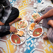 People enjoy Pao Bhaji, a favorite Mumbai snack, while sitting on a mat on the ground at Chowpati beach. Mumbai, August 2009