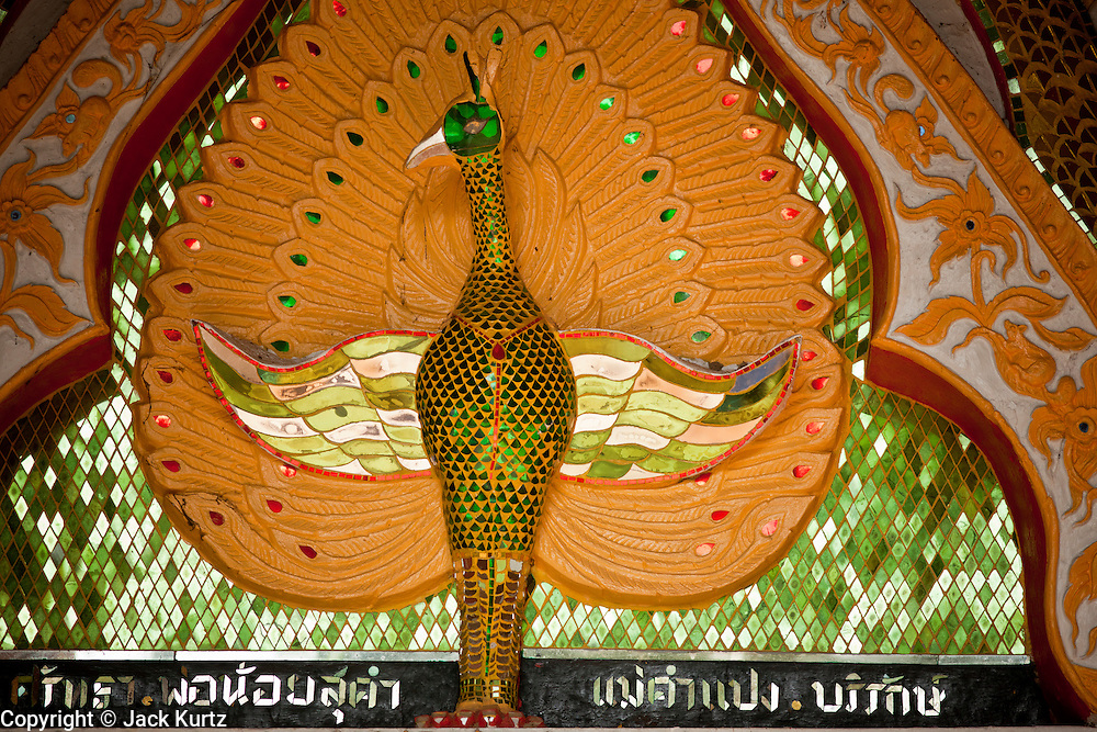 """28 JUNE 2011 - CHIANG MAI, THAILAND:  A peacock over the door to the """"viharn"""" or lecture hall, at a Buddhist temple near Chiang Mai, Thailand. Temple in northern Thailand were built in a variety of styles including Laotian, classical Thai, Lanna (also called northern Thai) and Burmese. The peacock over the door means the temple is built in the Burmese style and probably has a history of close ties with Chiang Mai's Burmese population, which in the past included teak traders.  PHOTO BY JACK KURTZ"""