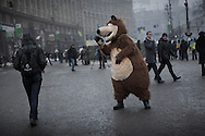 An anti-government protester walks to  Maidan Square, undistracted by an activist disguised as a bear, on December 12, 2013 in Kiev, Ukraine. Thousands of people have been protesting against the government since a decision by Ukrainian president Viktor Yanukovych to suspend a trade and partnership agreement with the European Union in favor of incentives from Russia was made recently.