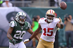 Sept 30, 2012; East Rutherford, NJ, USA; San Francisco 49ers wide receiver Michael Crabtree (15) reaches for a pass from San Francisco 49ers quarterback Alex Smith (11) while being defended by New York Jets cornerback Kyle Wilson (20) during the first half at MetLIfe Stadium.