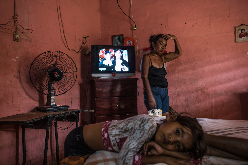 """LA VELA, VENEZUELA - SEPTEMBER 11, 2016: Minerba Piñero takes care of her elderly mother, Felipa Palencia de Piñero, who is diabetic, while her granddaughter, Karla Karina Piñero, 8, rests on the bed. Minerba also takes care of Karla, because her parents are working in Curacao. The family struggles to find the medicine that Felipa needs. To escape the crisis, Ms. Piñero's sister Maria spent all of her savings to pay smugglers to take her in a small fishing boat to Curacao island. """"I'm nervous,"""" she said. """"I'm leaving with nothing. But I have to do this. Otherwise, we will just die here hungry."""" Another benefit of living and working in Curacao, she said, is that she will be able to find and pay for her mother's medicines, and ship them to her in Venezuela.  Despite having the largest known oil reserves in the world, Venezuela is suffering from hyperinflation and a severe economic crisis making affordable food difficult for most middle and working class families to access.  Well over 150,000 Venezuelans have fled the country in the last year alone, the highest in more than a decade, according to scholars studying the exodus. As Hugo Chávez's Socialist-inspired revolution collapses into economic ruin, as food and medicine slip further out of reach, the new migrants include the same impoverished people that Venezuela's policies were supposed to help. """"We have seen a great acceleration,"""" said Tomás Paez, a professor who studies immigration at the Central University of Venezuela. He says that as many as 200,000 Venezuelans have left in the last year, driven by how much harder it is to get food, work and medicine — not to mention the crime such scarcities have fueled.  PHOTO: Meridith Kohut for The New York Times"""