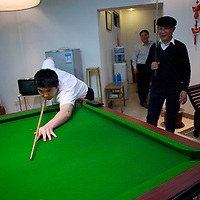BEIJING, 25. JANUARY, 2009 :   Mr. Li's  relatives play pool in the basement of his apartment on new years' eve  in Beijing .<br /> Mr. Li, a paper factory owner, is facing one of his most difficult times .&quot; Last November the market suddenly went down ,&quot; Li says.   <br /> He had bought paper, a lot of paper, and paid 7000 Yuan/ t .<br />  Li's company buys paper from paper mills and lives from the sales to publishing houses and other companies.  Since the market's collapse , he manages to sell the paper only for 6000 Yuan/t.<br /> His clients' export business to the USA had shrunk in Southern China. Mobile phone manufacturers don't need paper for the instruction guides to their mobile phones anymore as their US clients buys less China- made mobile phones.<br />  Toy manufacturers don't need paper anymore  because Americans import less toys from China. &quot; The crisis has driven many of my clients into bancruptsy&quot;, says Li.<br />  <br /> China's Communist Party  which will celebrate its 60th anniversary in October, currently faces its biggest challenge since the beginning of the economic reforms 30 years ago  : &quot; The phase of  rapid economic growth is over. For the first time the government is threatened with a  mistrust of a wide section of the population&quot;, warns the Communist party's Shang Dewen in Beijing.   <br /> Not only the China's poorest worry about the furture, but as well China's middle class is concerned about the crisis.     1,5 Millionen university graduates didn't find a job until the end of 2008  and this summer there'll be an additional  6,1 Million new graduates. More than 12 percent of university graduates face unemployment in 2009.
