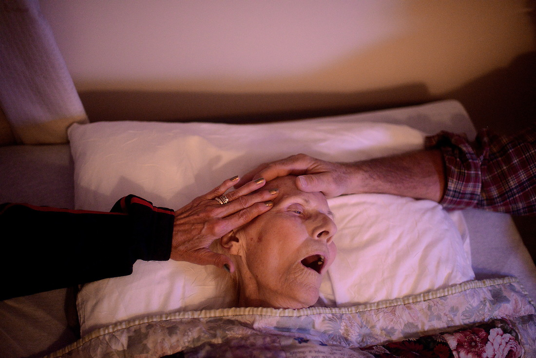 Son, Robert Lock and his wife Chris comfort his mother Mary as she takes her last couple of breaths in life on October 22, 2012, as she passes at a nursing facility in Gloversville, New York. Mary was 87 and placed in a nursing facility when she broke her femur over a year ago. — © /