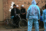 A little girl, right, peers at a man in a protective suit a couple of hundred meters away from the farm in the northern grasslands of the Inner Mongolia region in Tengjiaying, China in this Thursday Nov. 3, 2005 file photo. China said Sunday it can't rule out bird flu in the death of a 12-year-old girl last month and has called on the World Health Organization to help with diagnosis.