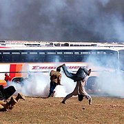 FUNERALS POLICE UNREST 19 APR 1993 - African national Congress and Communist Party supporters scatter as police fire teargas and live rounds outside the Soweto soccer stadium where the funeral of ANC leader Chris Hani was attended by hundreds of thousdans of mourners April 19, 1993. (Photo by Greg Marinovich )