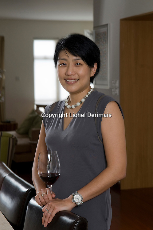 Judy Leissner, Grace Vineyards CEO photographed at home in Hong Kong in front of her 5 wine fridges which contains 1000 bottles.
