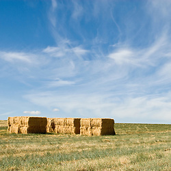 Stacked hay bales sit in a freshly cut field under blue bird skies in Central Oregon.