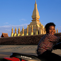 Asia, Laos, Vientiane, Portrait of boy sitting atop small motorcycle just outside Pha That Luang at sunset
