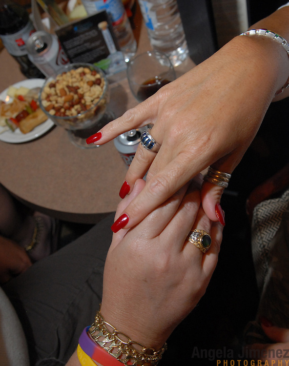 A couple holds hands at the Dinah Official Meet and Greet on March 28, 2007 at the Doral Desert Princess Resort in Cathedral City, California (just outside of Palm Springs), the opening event of five days of parties run by promoter Mariah Hanson's Club Skirts at the Dinah Shore weekend, an annual lesbian gathering run simultaneously with the Kraft Nabisco Championship LPGA golf tournament.