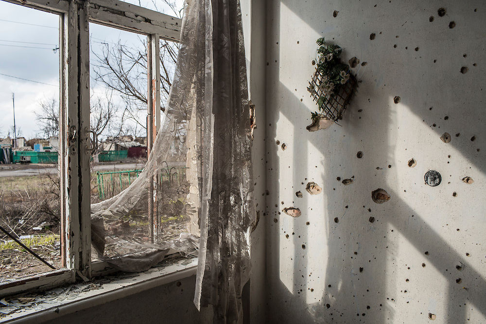 Scars from shrapnel caused by shelling dots the wall of a destroyed school on Sunday, March 27, 2016 in Nikishyne, Ukraine.