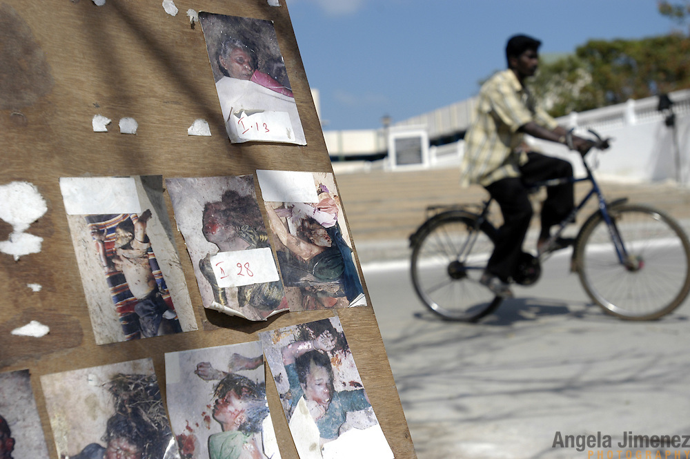 A man rides his bicycle past photos of unidentified tsunami victims in Vailankanni, in Tamil Nadu, India, on January 29, 2005, after the area was struck by the Indian Ocean Tsunami on December 26, 2004. Generated by an earthquake on the ocean floor, the tsunami devastated the fishing industry along the southeastern coast of India.