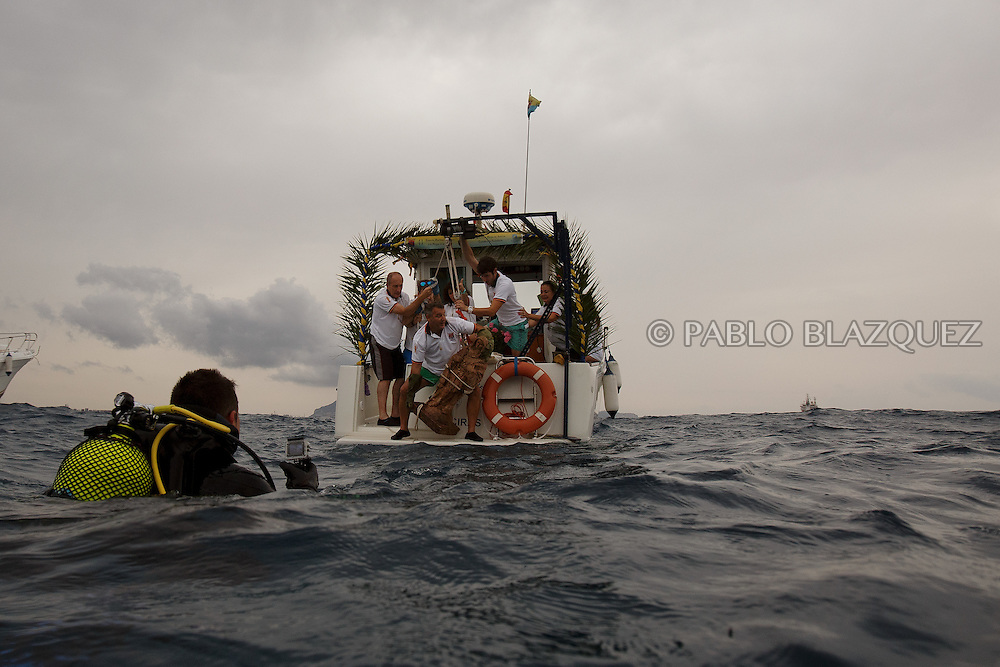 15/08/2016. Fishermen lift an sculpture of the Virgin of Palm on to a boat from the water during the yearly Virgin of Palm maritime pilgrimage on August 15, 2016 in Algeciras, Spain. The Our Lady of Palm maritime pilgrimage in Algeciras dates back to 1975 and takes place annually when fishermen rescue the submerged virgin from the deep sea. Worshippers amid thousands of visitors await its arrival at the Rinconcillo beach. The devotion for the Virgin of Palm comes from the seventeenth century when a ship coming from Italy docked at Algeciras port to wait out bad weather. According to legend, once the crew of the ship removed a box with an image of the Virgin from its cargo the weather turned and the sea's tides were calmed. (© Pablo Blazquez)