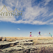 three young girls gleefully running and jumping for joy outdoors under the big montana sky