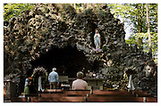 People visiting the replica of Lourdes's cave in the Maria Park in Meersel Dreef and praying to the holy Virgin Mary, mother of Jesus Christ. Meersel Dreef, Belgium, 2008