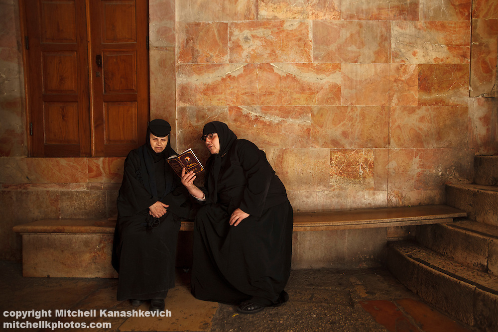 A Romanian nun reading a passage from the bible to her fellow nun in Church of the Holy Sepulchre, Jerusalem, Israel,Traditions and culture