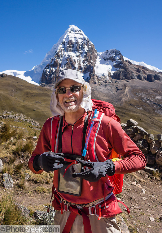A happy trekker carries an Apple iPad to record Nevado Trapecio (5653 m), which rises above Portachuelo de Huayhuash pass (4780 m). Day 4 of 9 days trekking around the Cordillera Huayhuash in the Andes Mountains, Peru, South America. For licensing options, please inquire.