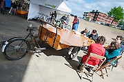 Mensen genieten van eten drinken aan een bakfiets met een uitklapbare tafel. In Nijmegen vindt voor de derde keer het International Cargo Bike Festival plaats. Het tweedaags evenement richt zich op het gebruik en de gebruikers van bakfietsen. Bakfietsen worden in heel Europa steeds vaker ingezet, zowel door particulieren als bedrijven. Het is een duurzame vorm van transport en biedt veel voordelen.<br /> <br /> In Nijmegen for the third time the International Cargo Bike Festival is hold. The two-day event focuses on the use and users of cargobikes. Cargo bikes are increasingly being deployed across Europe, both individuals and businesses. It is a sustainable form of transport and offers many advantages.Nederland, Nijmegen, 13-04-2014
