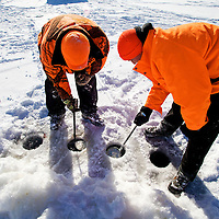 Clearing the newly drilled holes of ice before setting up an ice fishing shack on Lake Monona Bay in Madison, Wisconsin.