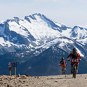 Starting from the top of Peak Express chairlift, mountain bikers ride down Whistler Peak in British Columbia, Canada. Castle Towers Mountain rises to 2676 meters elevation (8780 feet) in Garibaldi Provincial Park, in the Coast Range. The Resort Municipality of Whistler is popular for year-round  outdoor sports aided by gondolas and chair lifts.