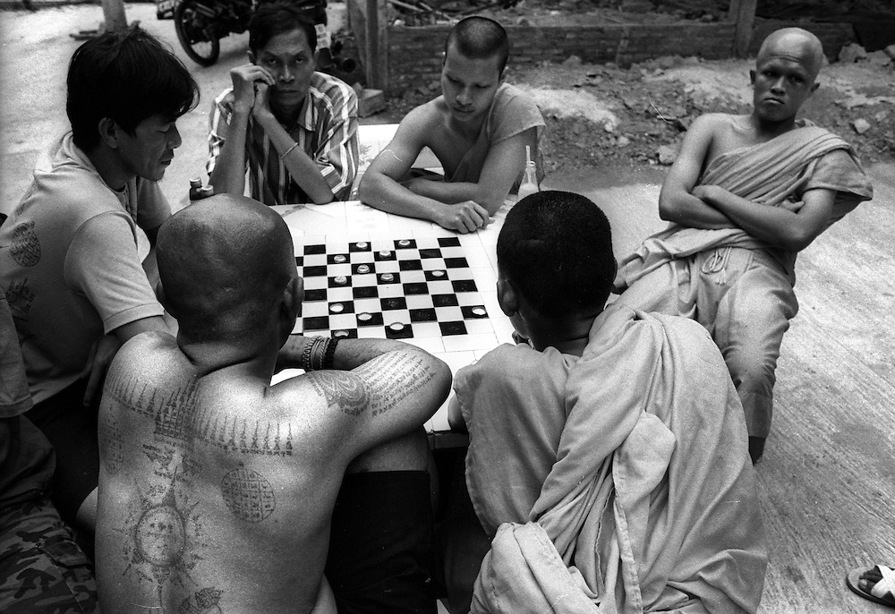 Tattoo Festival at Wat Bang Phra, a Buddhist temple in the town of Nakhorn Chaisri, Thailand - men adorned by Thai Monks with tattoos representing animal spirits often go into a trance claiming they are possessed  by the spirit of the animal. Here Monks take time out to play a board game..March 2003.©David Dare Parker/AsiaWorks Photography.